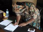 Commissioner Bridget Nagomoro signs affidavit for land for Ibba Girls School